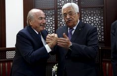 Palestinian President Mahmoud Abbas (R) clasps hands with FIFA chief Sepp Blatter during their meeting in the West Bank city of Ramallah May 20, 2015. REUTERS/Mohamad Torokman
