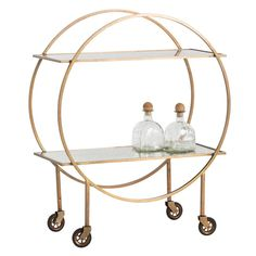 A Classic Deco statement piece, this bar features two shelves floating between parallel circles. The four legs each have rubber caster wheels, and the square iron tube frame is plated in antique brass. Shelves feature hand-applied antiqued mirror pattern which will vary. Designed for display and storage; not intended for commercial use. Finish may vary