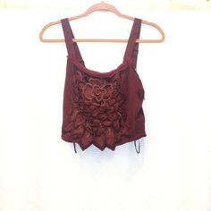 Free People flower crop top Edgy yet delicate crop top by Free People in the color Crimson.  The bottom of the top has unique edging that outlines the flowers.  Back has velvet details (see photo).  Never worn, tags still on however some threads are slowly coming out (not very noticeable and can probably be fixed by snipping with scissors). Free People Tops Crop Tops