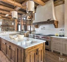 This kitchen features head-to-toe country decor including a plaster hood with hewn timber and corbels, a wood-beamed ceiling, and hand-molded tiles.