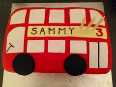 Red bus / double decker bus/ London bus cake. From The Treasure Hunter UK blog (www.thetreasurehunteruk.com) Easy to make - rectangular cake; cover in red roll-out icing; cut windows/doors from white roll-out icing (use a ruler to help cut them straight/similar sizes); use a glass as a template for the wheels; then use a strip of yellow for the name banner and write on the name with a tube of shop-bought writing icing.