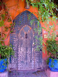 Beauteous Moroccan door flanked by two potted plants painted Majorelle blue.