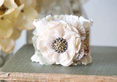 Description This cuff bracelet features pretty textiles, lace trim and an eye-catching vintage button with a beautiful floral design. A unique gift for women and girls who love to wear one-of-a-kind j