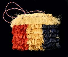 Kete Raakei (decorative basket/kit) made with harakeke (flax) fibre covered with red, white & blue lacebark loops  Collection of Te Manawa Art Society Inc.