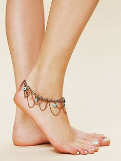 Beaded anklet with tassel and metal chains.