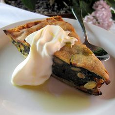 Swiss chard, raisin & pine nut tart, with dollop of sour cream; drizzle of olive oil.