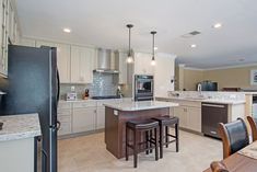 If you have a large enough U-Shaped kitchen, consider adding an island.  For a bonus - make the cabinet color and countertops different from the perimeter of the kitchen! #kitchen #design #ideas