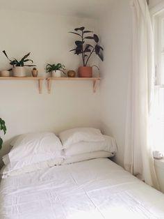 Une chambre à l'espace restreint, mais qui ne semble pas étouffante grâce au blanc dominant et à la présence de petites plantes vertes !