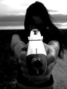 Girl holding a gun close up