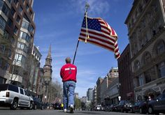 Lt. Mike Murphy of the Newton, Mass., fire dept., carries an American flag down the middle of Boylston Street after observing a moment of silence in honor of the victims of the bombing at the Boston M