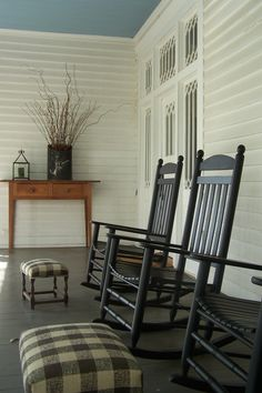 Client porch, long veranda, rocking chairs, foot stools, black and white check fabric, front door, table, blue ceiling, white house
