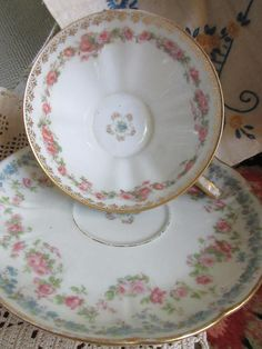 Here is an exquisite cup and saucer by Haviland, made in France at the turn of the 1900s. The Hallmark is Wright, Tyndale and Van Roden. Hold it to the light and you can see the other side. Both the cup and the saucer are lightly scalloped they are decorated with tiny pink flowers and blue flowers, and little lines of gold stylized fleur de lys on the inside rim. There is a floral motif at the bottom of the cup. What I really love about this cup is how the handle is shaped like a ribbon…