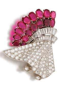 An Art Deco ruby and diamond double clip-brooch, Le Roy et Fils Ltd, 1930s. Of abstract design, claw-set with oval rubies, pavé-set with circular- and single-cut diamonds, linked by baguette diamond lines, detaches to be worn as two clips, each signed Le Roy et Fils, one numbered, brooch fitting detachable. #LeRoy #ArtDeco #DoubleClip