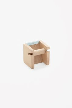 Made from beech wood, this tape holder has a modern geometric shape and comes with three rolls of tape.