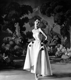 1952 Barbara Mullen in white silk faille evening dress decorated with mink pom-poms, a Bendel Original, Henri Bendel.
