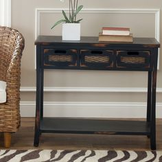Decorate your home with one of these rustic console tables with storage from Corby. This distressed black console table features three drawers for added storage and inset wicker drawer fronts. The table measures 30' H x 34' W x 14' D.