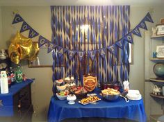 Police Academy graduation party on a budget.  I printed out the banner letters form shanty-2-chic.com and glued them to black and blue card stock. Used some twine to loop it together and wah-lah!  Blue and black tablecloths/streamers from Party City, personalized LEO plaque from a kiosk in my mall. He LOVED it and was so touched. Cost for decor was about $25! Streamers are the easiest DIY decor!