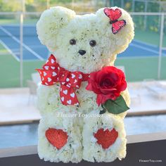 EXCLUSIVE All New FlowerToy® Silk Collection! Hand-crafted from silk flowers in the shape of an adorable bear, complete with eyes, nose and a stylish bow tie. Shipped in a bright red gift box.