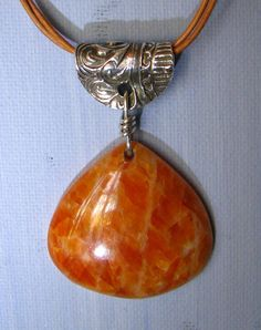 I have suspended this lively Orange Calcite onion-shaped pendant from a silver metal clay (PMC3) bail and a natural leather cord -- knotted to be