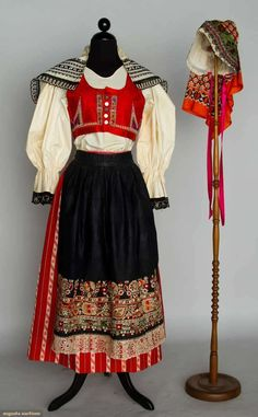 Woman's Folk Costume, Czechoslovakia, C. 1930, Augusta Auctions -- Muslin blouse w/ black lace, wool skirt w/ red & white stripes, apron colorfully embroidered on indigo cotton, vest of magenta brocade w/ red trim, bonnet of brocade & metallic lace w/ orange & black cotton print back crown, white shoulder scarf w/ black embroidery.