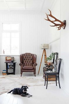 Manly seating area featuring brown leather armchair, tripod lamp, mounted antlers, cowhide rug, and vintage decor.