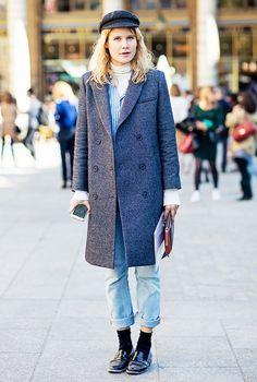 Street style look com camisa listrada, blazer longo cinza, blusa gola bege, calça jeans, sapato masculino aparente.