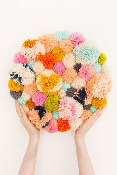 For those of us that don't have the knack for woven versions, let me introduce you to this cute little DIY pom pom wall hang instead!