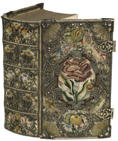 Band of white silk 1665 - 1620 White silk, embroidered silk, metal partly in relief, beads and sequins. Wooden boards, gilt silver corner pieces and locks Bindings of the Royal Library