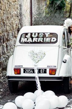 Voiture des mariés décorée de lettres et cœur en carton, recouverts de fleurs articielles