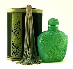 """Lalique perfume bottle for Roger et Galle """"Le Jade"""" in opalescent green glass with molded labeling, yellow ochre patina, in silk box with tassel. Description from pinterest.com. I searched for this on bing.com/images"""