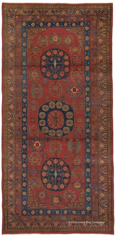 KHOTAN, Central Asian (SOLD), 6ft 11in x 14ft 3in, Circa 1800. This is a quintessential connoisseur-level Khotan corridor carpet from the weaving tradition at the turn-of-the 19th century in northwestern China. An exceptional range of breathtaking colors, continual color shading, and extremely lustrous wool elevate this precious rug to its top tier category. Note the early rendering of the three circular field medallions and the endless knot border.