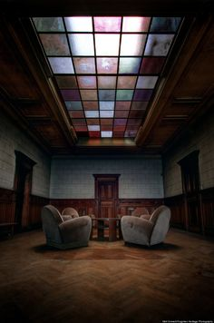 """Belgium Chateau Interior  """"Chairs and a coffee table sit in a pool of light below a beautiful skylight in a European mansion."""""""
