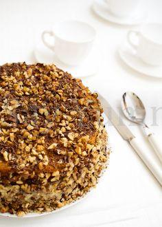 La torta alla crema con le noci si prepara con un semplice impasto lievitato, farcito con crema pasticcera e guarnito con granella di noci e cioccolato.