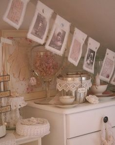 Fabric garland with pictures of little children.  Dresser decorated  very dainty, with lace, jar of cute stuff, frame with gloves and jewelery, tea cup and roses.,