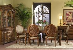 Banana leaf carvings, woven raffia accents, custom designed hardware and an antiqued tropical brown finish give this dining collection a refreshing Caribbean style. Features fancy–face primavera veneers with white ash burl borders and racetrack inlays.