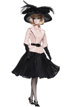 The perfect afternoon suit begins with a pink jacket featuring ¾ length sleeves and trompe l'oeil vest. Faux patent leather belt is the perfect accent piece. Sheer black pleated skirt lends feminine flair. The classic accouterments for this ensemble: black stilettos and gloves. Finally, the picture hat with lavish feather embellishments completes the look.