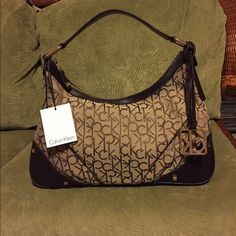 """Calvin Klein Hudson Signature Hobo Bag •Color: Khaki/Brown •Faric; Trim: Leather; Lining: Cotton •Shoulder strap with 8"""" drop •Top zip closure •Detachable CK logo charm, square logo-stamped, back zip pocket •Interior wall zip pocket, 2 open pockets •Measurements 15""""wide, 10""""Height, 4""""D. •There is a slight scratch on the leather bottom of the purse (last picture). Calvin Klein Bags Shoulder Bags"""