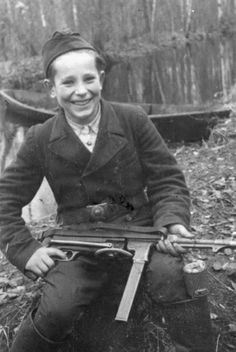 "Fifteen-year old Misha Petrov fought as a partisan choosing the name of ""Stalin."" He is pictured with his captured German MP3 SMG and a Soviet anti-personnel hand grenade RGD-33 stuffed in his boot. The photo was taken in Belarus, in 1943."