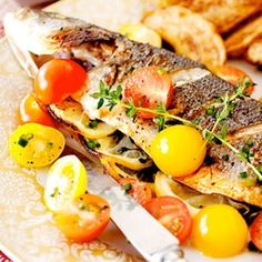 A bright colored Greek fish.Tomatoes are soaked in vinegar and garlic join the whole fish on the grill.