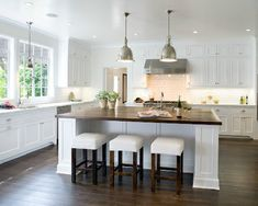 White shaker kitchen cabinets to ceiling with calcutta marble counter tops, white kitchen island with butcher block counter top, industrial yoke pendants, white slip-covered stools, subway tiles backsplash. Kitchen Cabinets To Ceiling, White Shaker Kitchen Cabinets, Kitchen Windows, White Cabinets, Tall Cabinets, Cherry Cabinets, New Kitchen, Kitchen Decor, Summer Kitchen