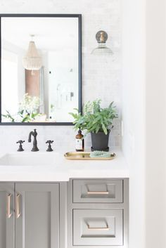 PURE SALT INTERORS // TALEGA BEACH HOUSE PROJECT // MASTER BATHROOM // brass hardware, marble, sconces, potted plant, beaded chandelier, brass tray..