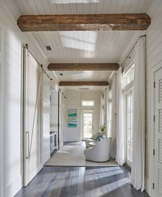 This hallway boasts rustic wood beam ceiling, shiplap walls, shiplap ceiling as well a wall of French doors and transom windows dressed in white cotton curtains.