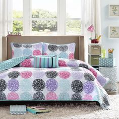 Add color to your bedroom with this Audrina coverlet set by Mi-zone. Doodled circles create this look with pops of pink, teal, purple and black while a teal polka dot reverse plays up the back.