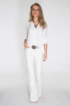 Camisa branca fluida, peça curinga e super democrática. Combinada com a calça flare de tecido listrado, compõe o look total white, super sofisticado. O cinto com maxi fivela e o colar de correntes dão ar moderno.