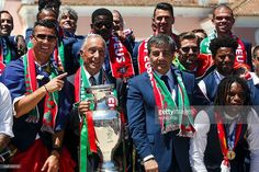 Portugal's forward Cristiano Ronaldo (L) accompanied by Portugal's President Marcelo Rebelo de Sousa (2ndL) and other team members celebrate their victory on July 11, 2016 after their Euro 2016 final football win over France yesterday. The Portuguese football team led by Cristiano Ronaldo returned home to a heroes' welcome today after their upset 1-0 win triumph over France in the Euro 2016 final. FOX