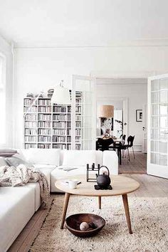 Homes: Danish: the living room with a coffee table and bookshelves in the background