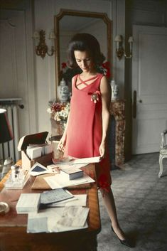American socialite (and the younger sister of Jacqueline Kennedy Onassis) Lee Radziwill photographed in a coral Dior dress inside the office of her home, London, England, 1960, photograph by Mark Shaw for LIFE magazine.