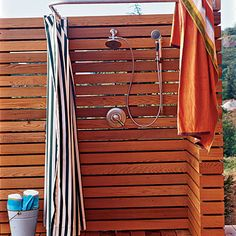 This outdoor shower uses treated wood, rust-resistant fixtures, and an outdoor-fabric curtain to withstand harsh coastal conditions.