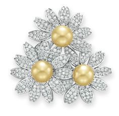 A CULTURED PEARL AND DIAMOND BROOCH, BY TIFFANY & CO.   Designed as three flower blossoms, each set with a golden cultured pearl measuring approximately 8.90 mm, extending circular-cut diamond petals, mounted in platinum  Signed Tiffany & Co.