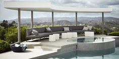 The pool deck features a custom-made sectional, upholstered in a Perennials fabric, and concrete side tables by Ernsdorf Design; the pool is sheathed in tiles by Villeroy & Boch.